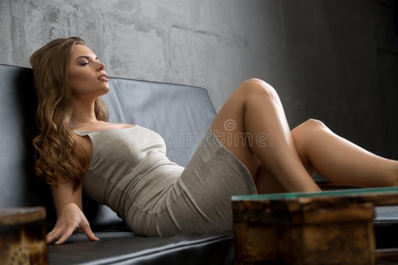 Sexig flicka som kopplar av på den trevliga soffan i studio royaltyfri bild