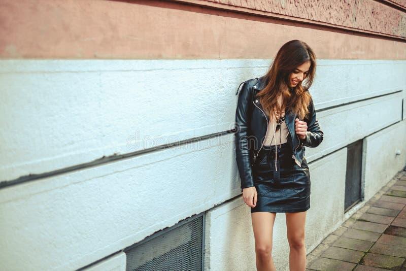 Sexig flicka som ler och lutar på väggen fotografering för bildbyråer