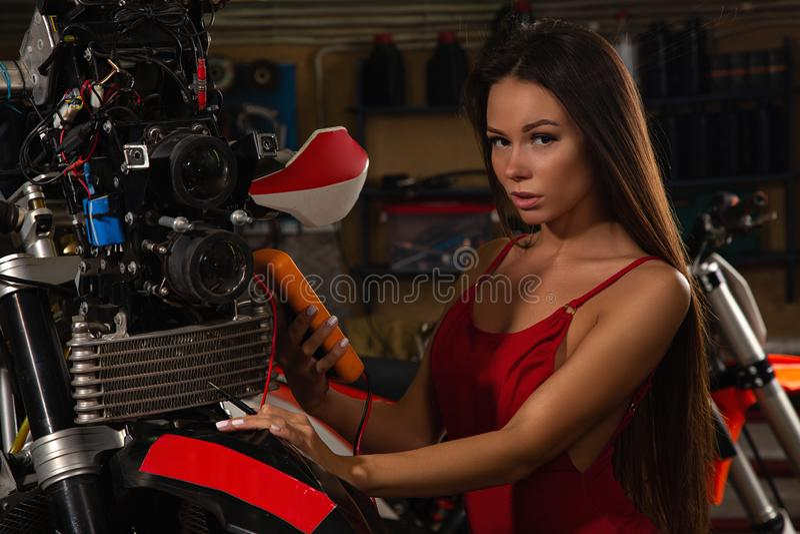 Sexig flicka som reparerar motorcykeln royaltyfria bilder