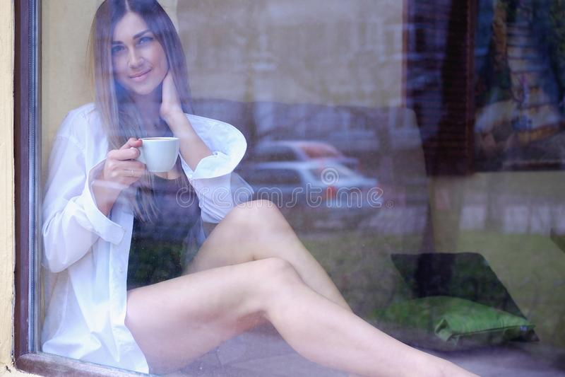 Sexig flicka som sitter nära fönstret och dricker kaffe enkel lycklig kvinna i vita mäns skjorta som ut ser fönstret fotografering för bildbyråer