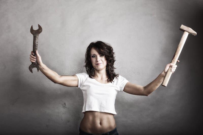 Sexig flickainnehavhammare och skiftnyckelskruvnyckel fotografering för bildbyråer