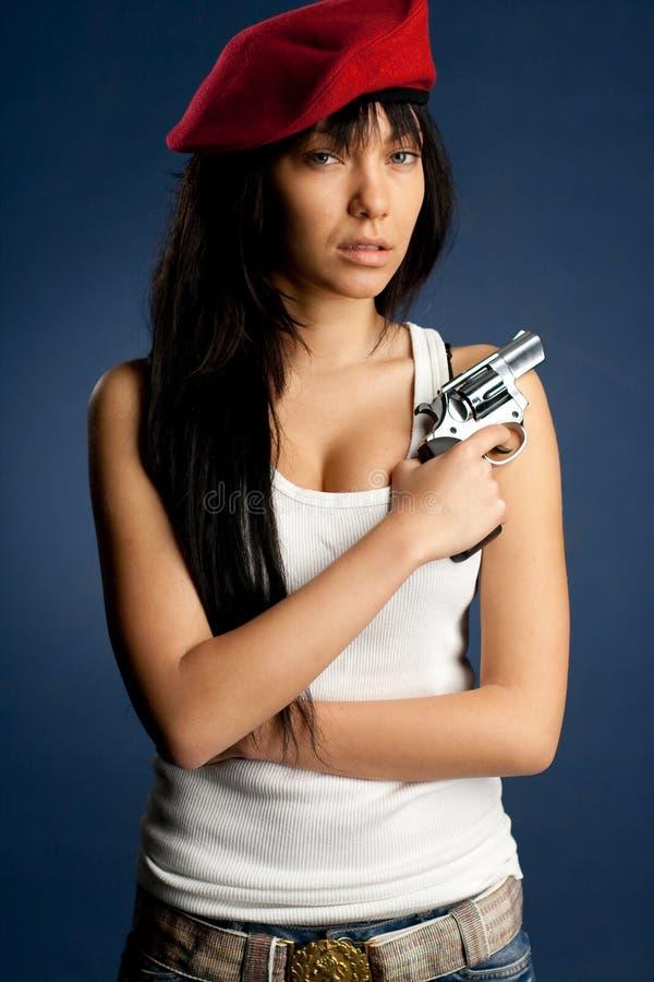 Sexig flickawhit ett vapen en röd baret arkivbild