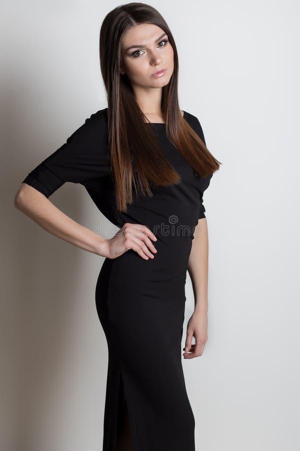 Sexig härlig elegant kvinna med långt hår, ljust aftonsmink i en svart aftonklänning i studion på en vit bakgrund royaltyfria bilder
