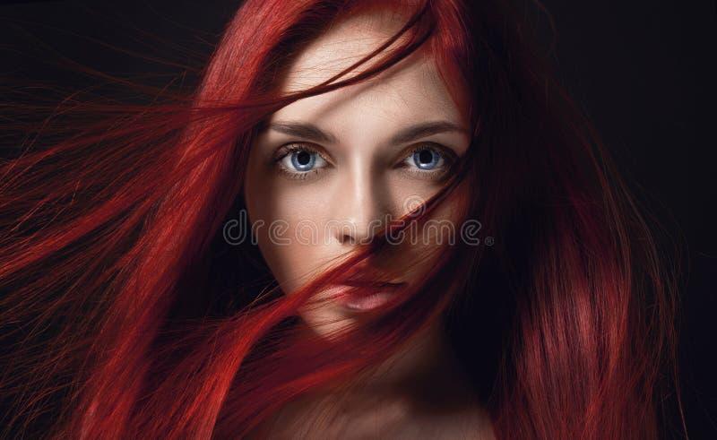 Sexig härlig rödhårig manflicka med långt hår Perfekt kvinnastående på svart bakgrund Ursnyggt hår och djupa stora blåa ögon arkivbilder