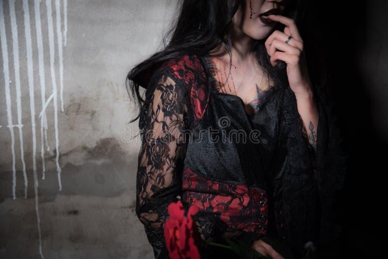 Sexig härlig vampyr som är hungrig och finner för blod i övergett hus-, allhelgonaaftonfestival-, fasa- och skönhetmodebegrepp, royaltyfria foton