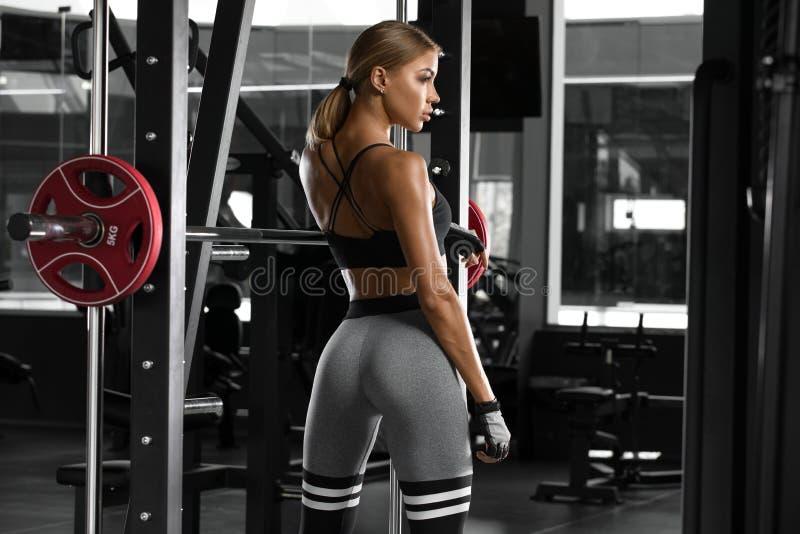 Sexig idrotts- flicka som utarbetar i idrottshall göra övningskonditionkvinnan Härlig ände, i att lägga benen på ryggen royaltyfria foton