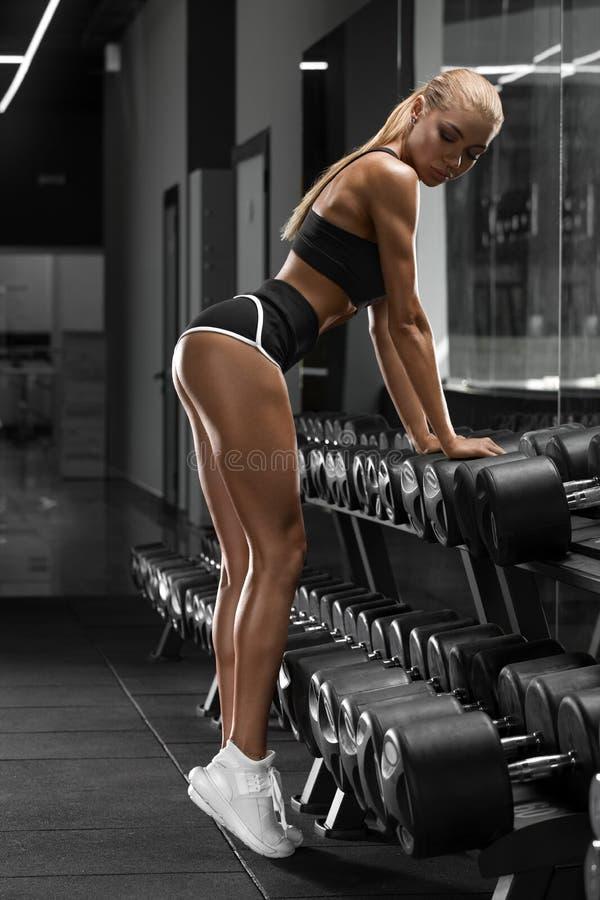 Sexig idrotts- flicka som utarbetar i idrottshall göra övningskonditionkvinnan Sexig härlig ände i läderrem fotografering för bildbyråer