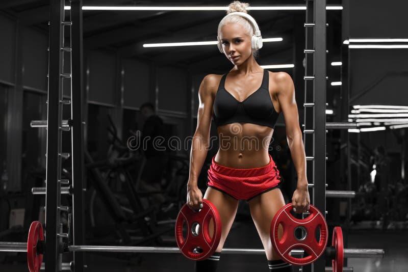 Sexig idrotts- kvinna som utarbetar i idrottshall Konditionflicka som gör övningen, muskulös kvinnlig royaltyfri foto