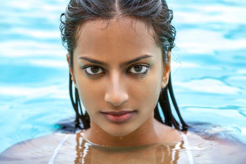 Sexig indisk asiatisk kvinnaflicka i simbassäng royaltyfri foto