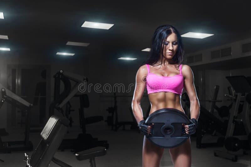 Sexig konditionkvinna i sportkläder med den perfekta konditionkroppen i idrottshall arkivfoton