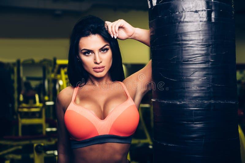 Sexig konditionmodellkvinna som poserar nära att stansa påsen i sportidrottshall royaltyfria bilder