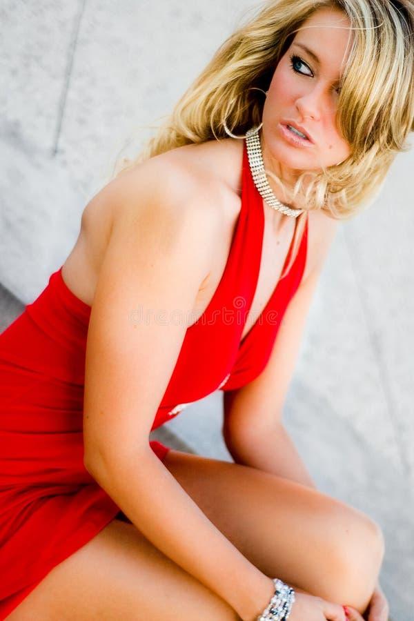 Sexig kvinna - blond modell i formell röd klänning arkivbild