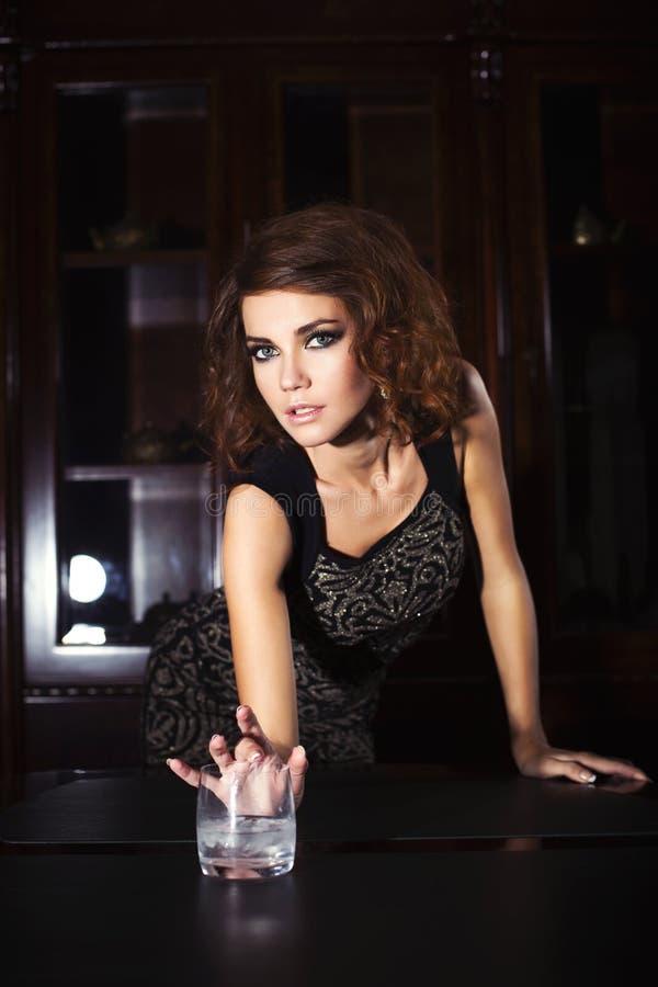 Sexig kvinna för brunett i tillbaka ljus stående near tabell med drycken arkivbild