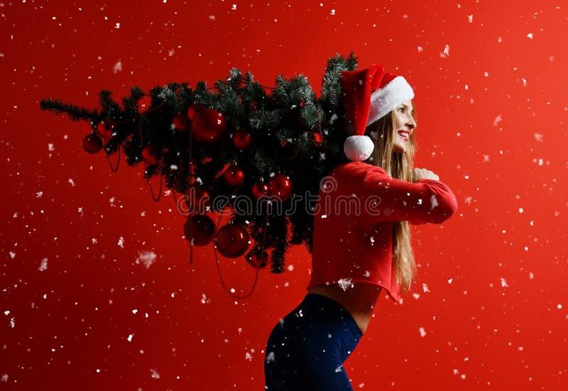 Sexig kvinna för julkonditionsport som bär den santa hatten som rymmer xmas-trädet på hennes skuldror snowflakes royaltyfri fotografi