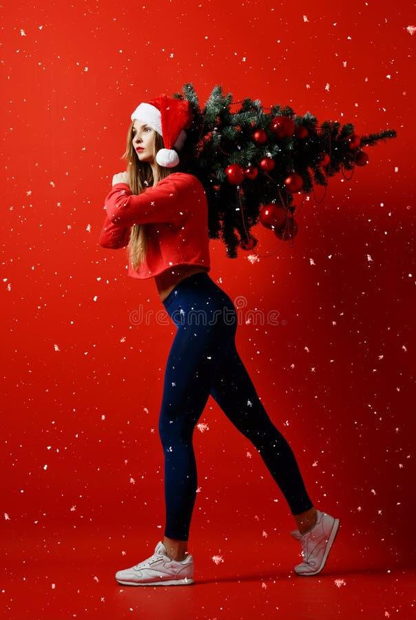 Sexig kvinna för julkonditionsport som bär den santa hatten som rymmer xmas-trädet på hennes skuldror snowflakes royaltyfri bild