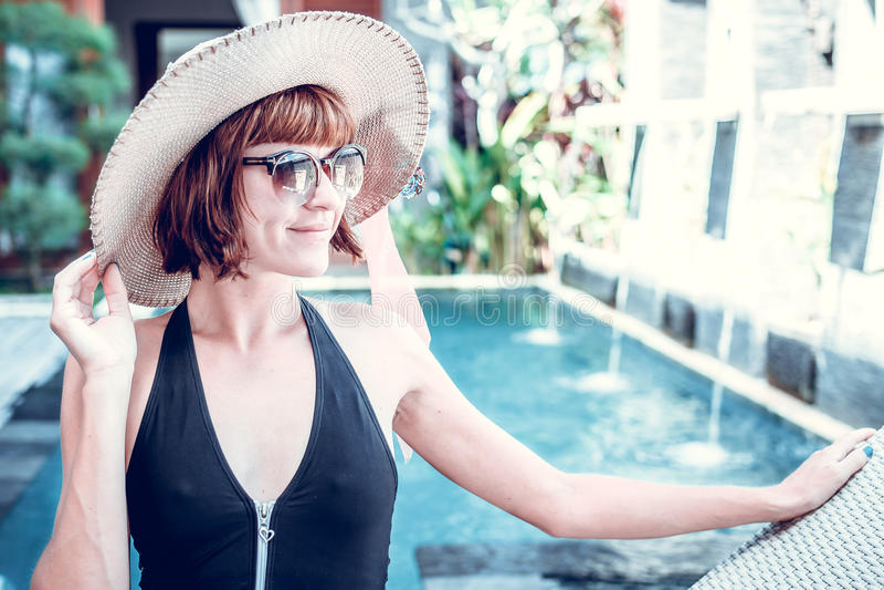 Sexig kvinna för skönhet med hatten och solglasögon som tycker om hennes sommarsemester på simbassängen på en lyxig villa Sommar fotografering för bildbyråer