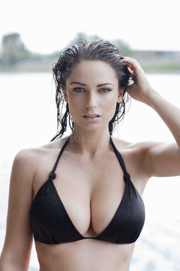 Sexig kvinna i bikini med vått hår och stora mesar arkivbilder