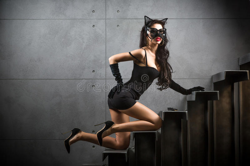 Sexig kvinna i catwomandräkten som ligger på trappa royaltyfria bilder