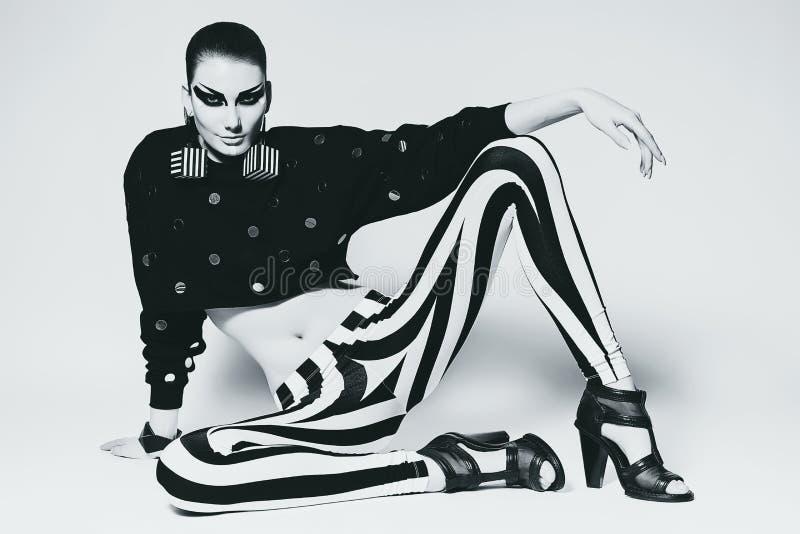 Sexig kvinna i damasker med band som sitter på golvet arkivbilder