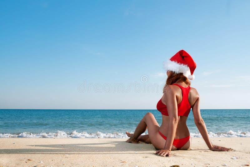 Sexig kvinna i den santa hatten på havet arkivbilder