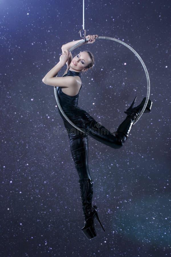 Sexig kvinna i latexcatsuit som hänger på flyg- beslag på natten royaltyfria foton