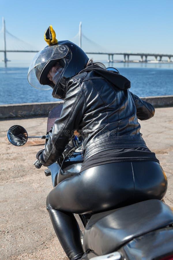 Sexig kvinna i svartläderkläder som sitter på cykeln som tillbaka ser royaltyfri bild