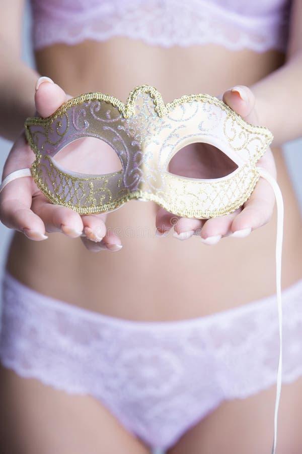 Sexig kvinna i underkläderna som rymmer en maskering arkivbild