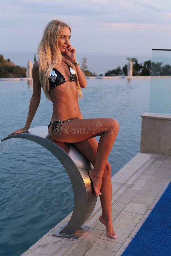 Sexig kvinna med blont hår i den eleganta bikinin som poserar nära luxurio royaltyfri fotografi