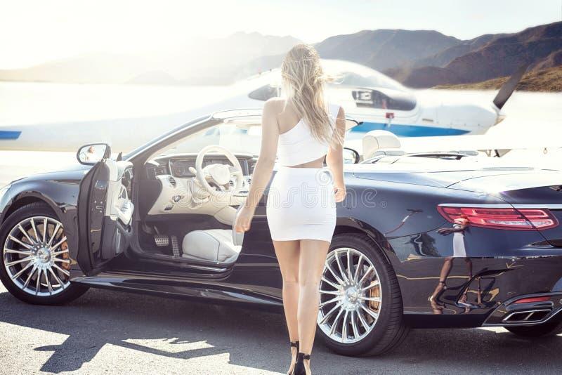 Sexig kvinna med den lyxiga bilen och flygplanet arkivfoto
