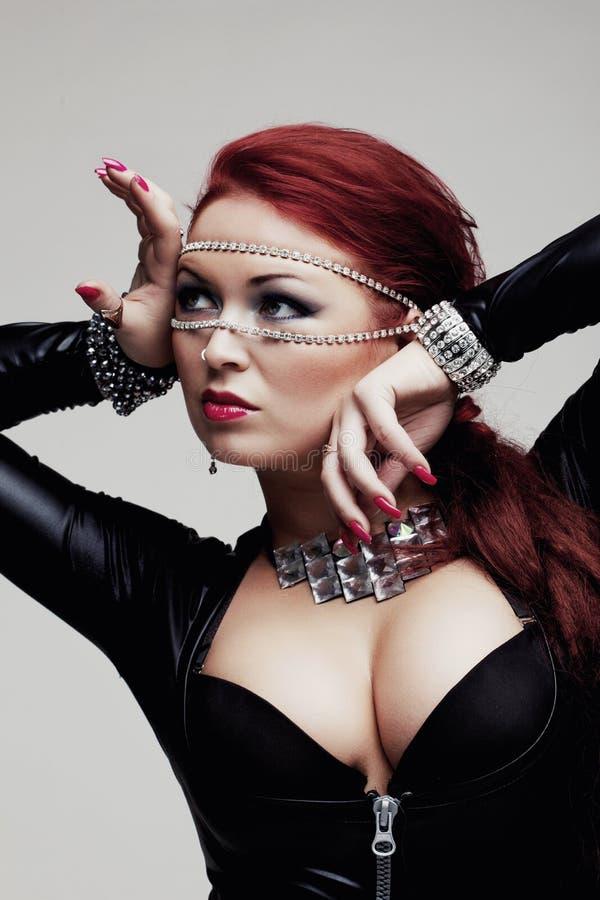 Sexig kvinna med det enorma bröst i latexdräkt arkivfoton