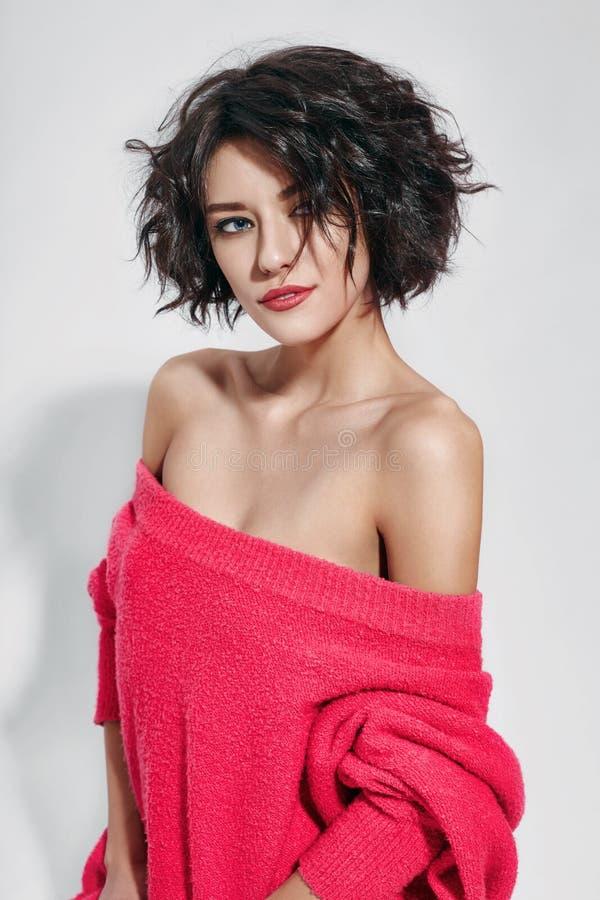 Sexig kvinna med kort hår som klipps i rosa röd tröja på vit bakgrund Perfekt flicka med vått ovårdat mörkt hår och ljus makeup royaltyfria bilder