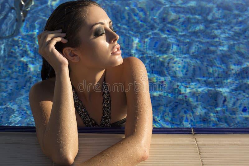 Sexig kvinna med långt hår i bikini som kopplar av i simbassäng royaltyfri foto