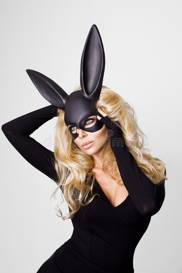 Sexig kvinna med stora bröst som bär ett svart anseende för maskeringspåskkanin på en vit bakgrund fotografering för bildbyråer