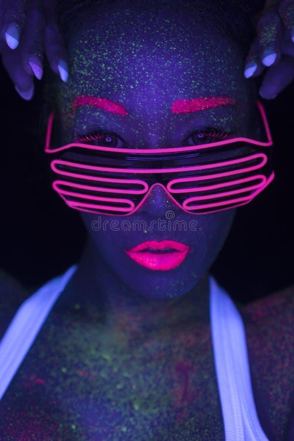 Sexig kvinna med UV fluorescerande framsida- och kroppmakeup royaltyfri fotografi