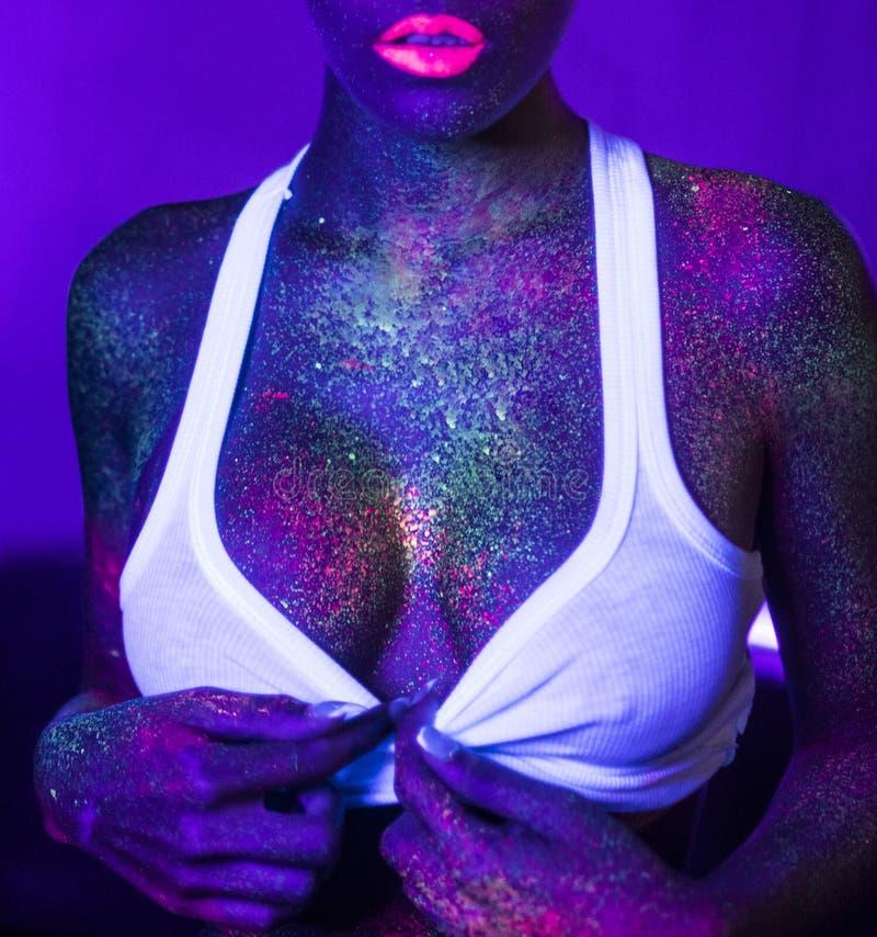 Sexig kvinna med UV fluorescerande framsida- och kroppmakeup arkivfoto