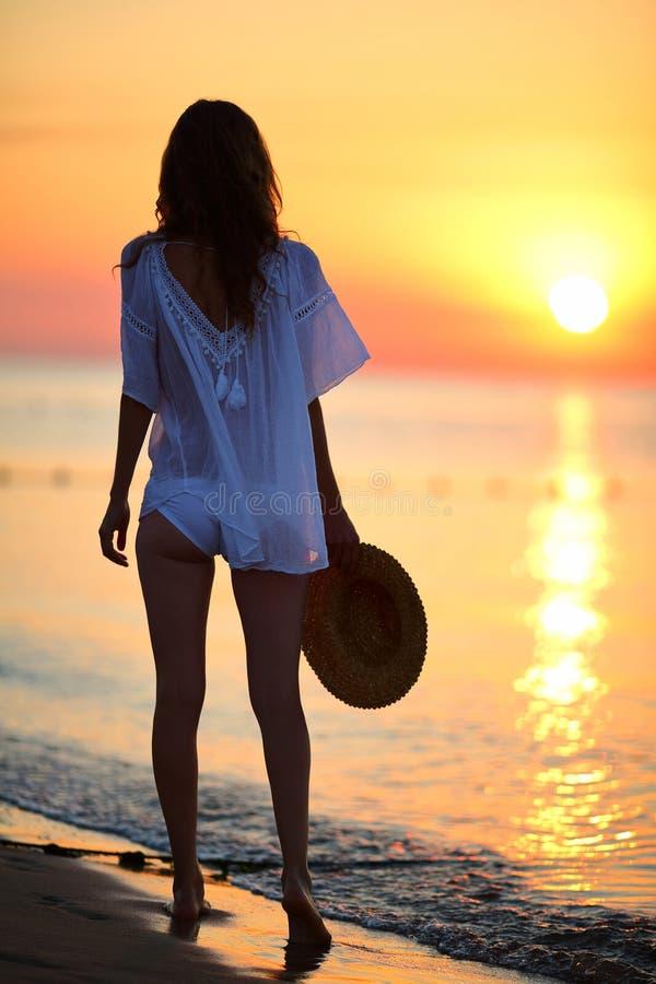 Sexig kvinna som går på stranden på soluppgång royaltyfri bild