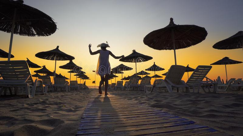 Sexig kvinna som har gyckel som går på stranden på solnedgången arkivfoto