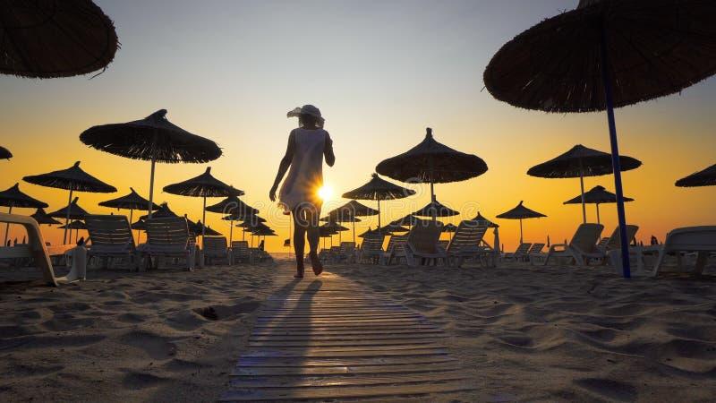 Sexig kvinna som har gyckel som går på stranden på solnedgången arkivfoton