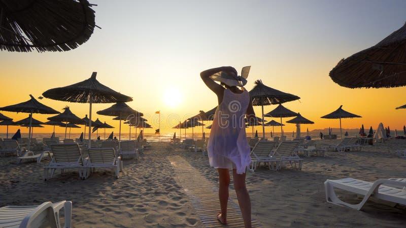 Sexig kvinna som har gyckel på den tomma härliga stranden med sugrörparaplyer royaltyfri fotografi
