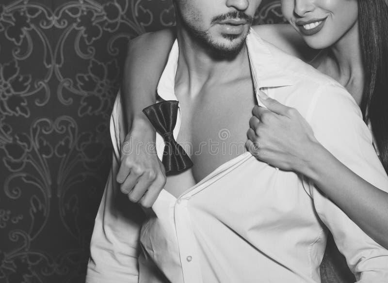 Sexig kvinna som klär av moderiktiga den inomhus svartvita macho mannen royaltyfria foton
