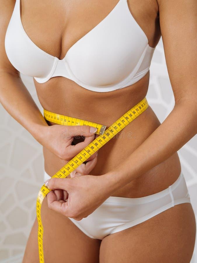 Sexig kvinna som mäter hennes slanka midja arkivfoto