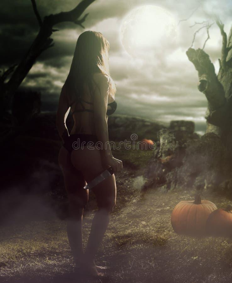 Sexig kvinna som rymmer en kniv i skogen arkivfoton