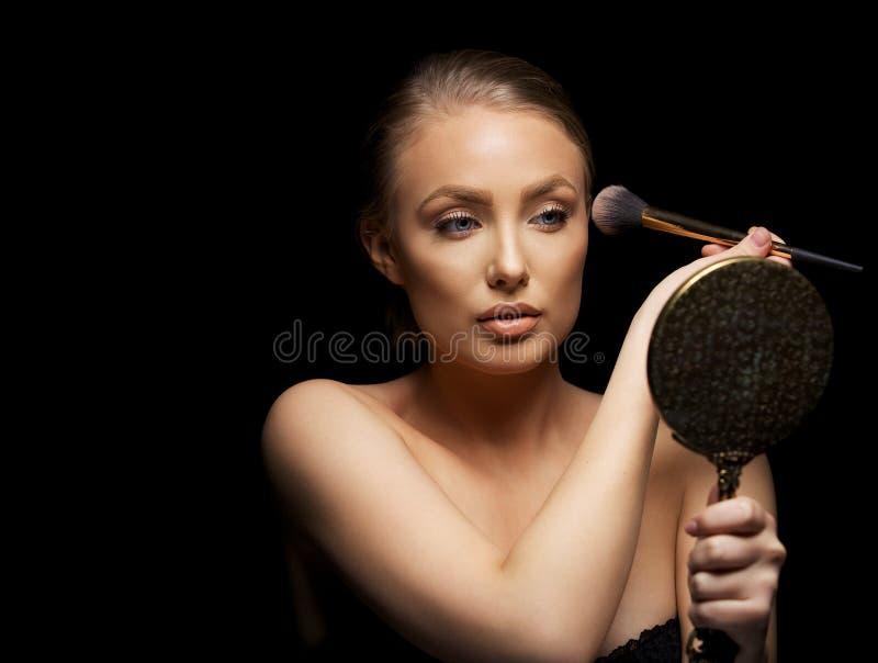 Sexig kvinna som sätter på smink arkivbild