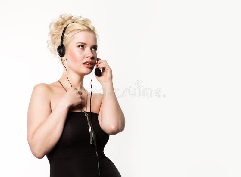 Sexig le kvinna som arbetar i en appellmitt Hörlurar med mikrofontelefonförsäljningkvinna som talar på helpline Fritt avstånd för arkivfoton