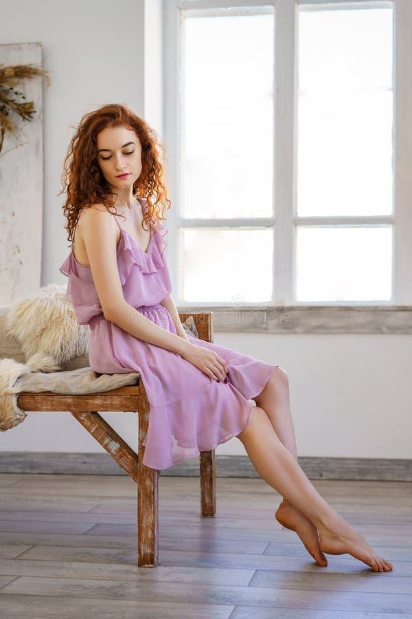 Sexig lyxig kvinna i adress Moderödhårig man i den härliga klänningen som poserar sammanträde i studio Härligt hår och en perfekt royaltyfri fotografi