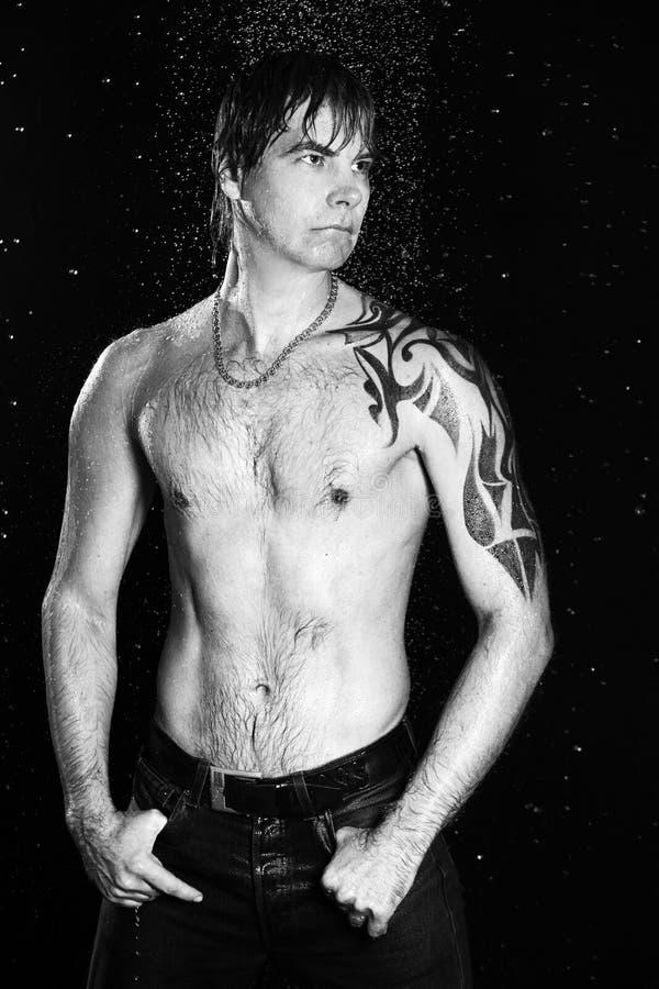 Sexig man i duschaquastudio royaltyfri bild