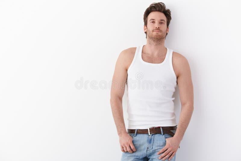 Sexig man som plattforer, genom att le för vägg arkivfoto