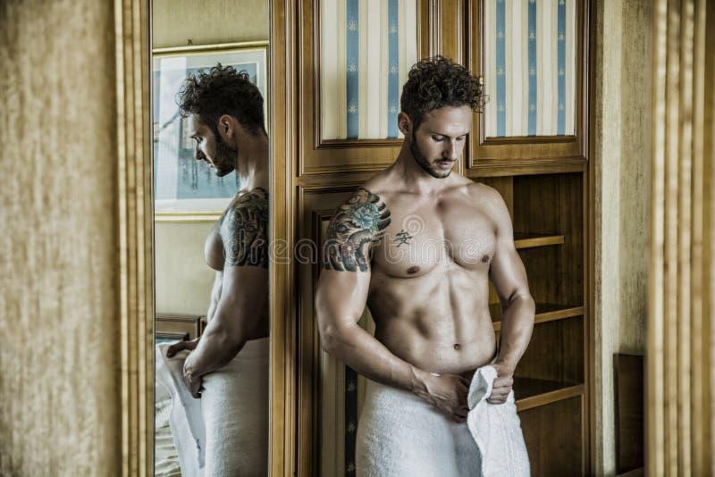 Sexig man som står shirtless i sovrum royaltyfria foton