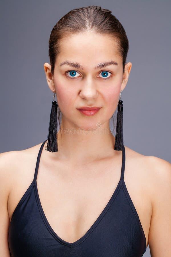 Sexig modebrunettkvinna i svart baddr?kt fotografering för bildbyråer