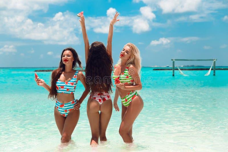Sexig modell för bikini som tre har gyckel på den tropiska stranden, exotisk Maldiverna ö Lyckliga le kvinnor, i att posera f fotografering för bildbyråer